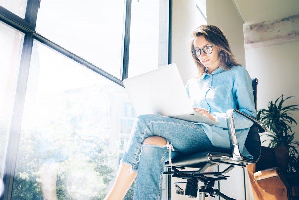 Woman using her laptop beside the window