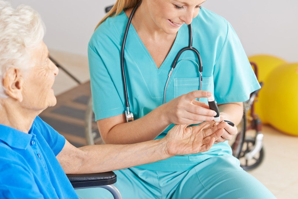 nurse monitoring blood sugar of old woman