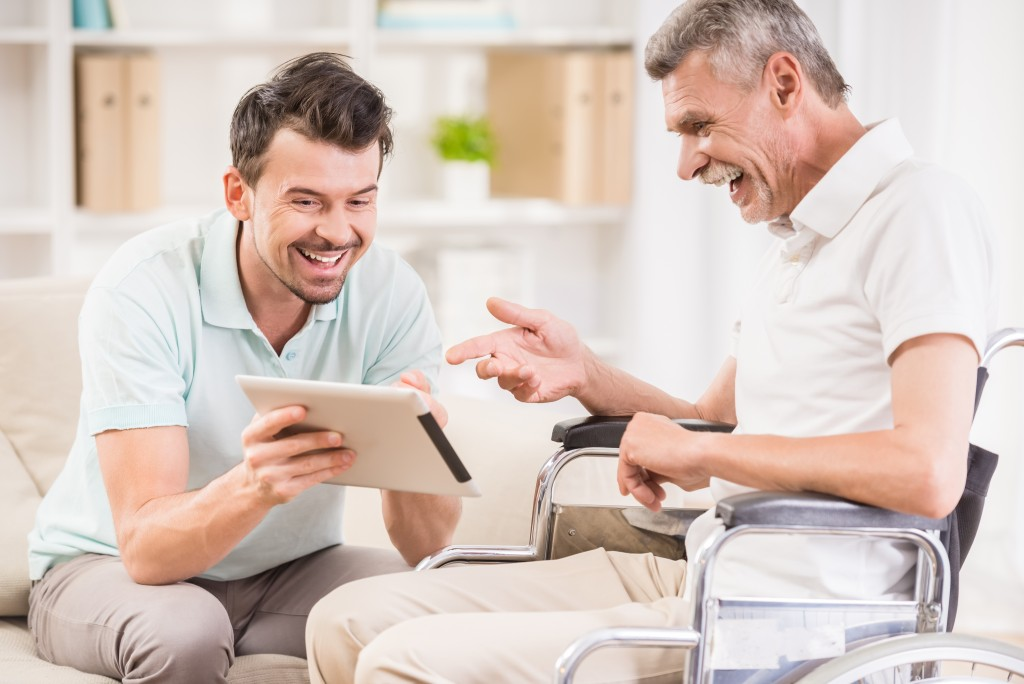 caregiver and old man holding a tablet