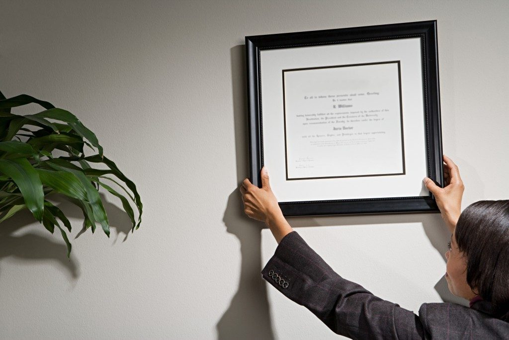Businesswoman hanging framed certificate